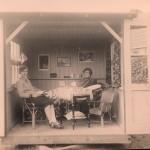 Tbc- patiënte ontvangt bezoek in haar huisje. De deuren open voor ventilatie en meedraaiend met de zon op een draaischijf.